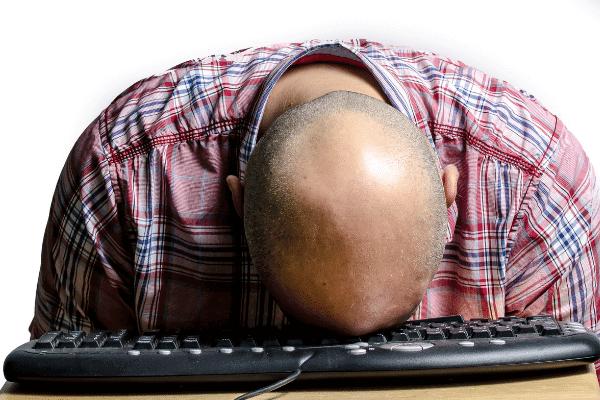 איש עם קרחת עם הראש על המקלדת של המחשב