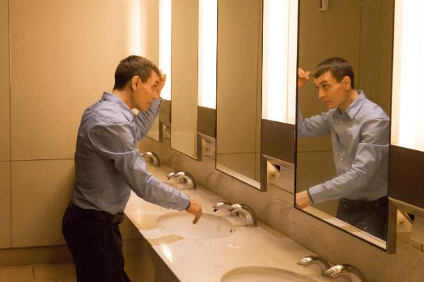 איש מסתכל על השיער שלו במראה